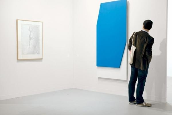 Посетитель ярмарки Art Basel Miami Beach рассматривает работу Элсворта Келли