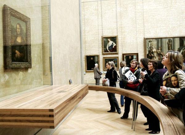Туристы, изучающие «Мону Лизу», огороженную барьером и защищенную пуленепробиваемым стеклом