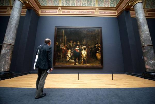 Посетитель смотрит на картину Рембрандта «Ночной дозор» в экспозиции обновленного Рейксмузеума в Амстердаме
